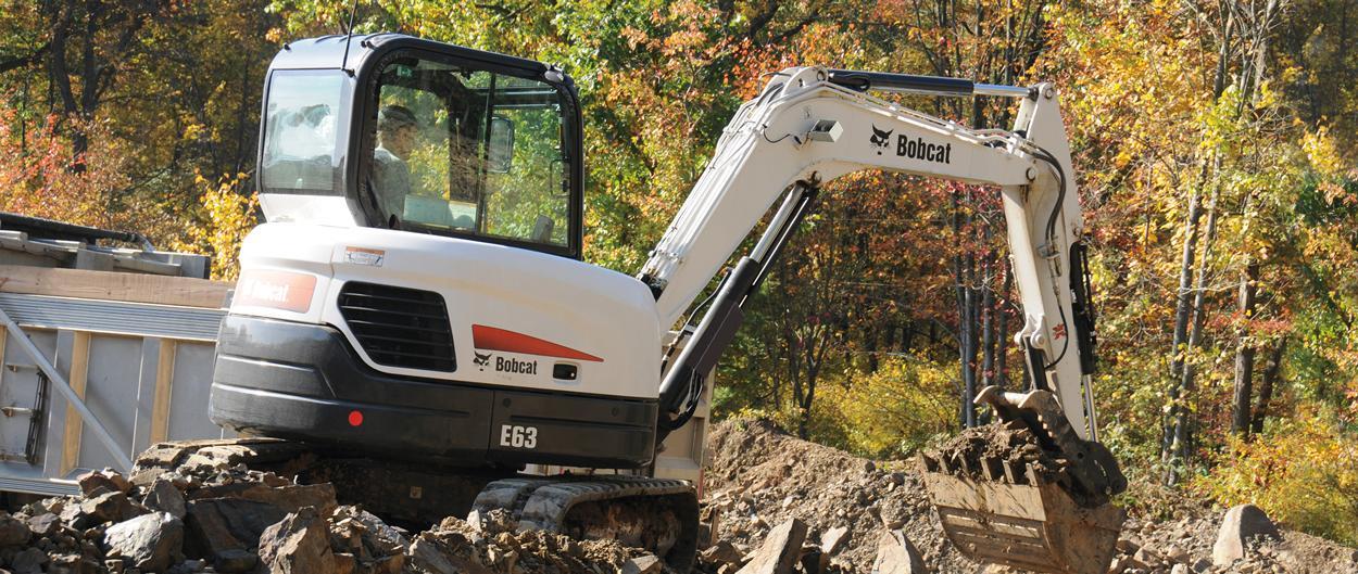 Bobcat E63 compact excavator loads truck.