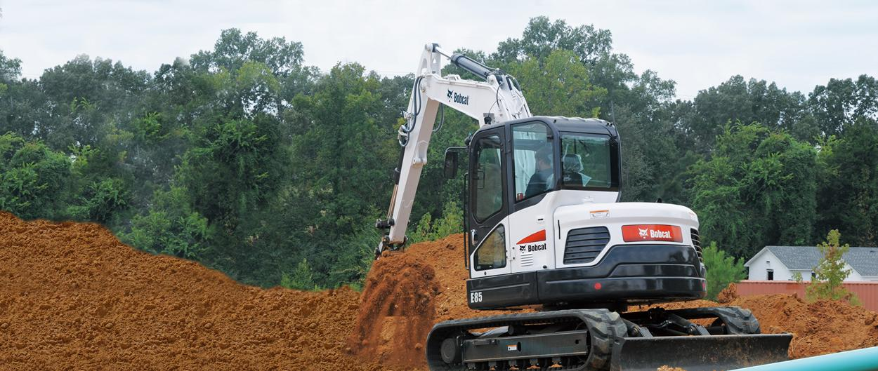 Bobcat E85 compact excavator digs trench.