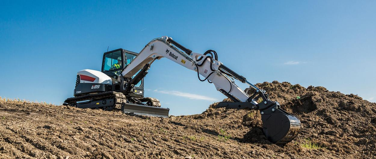 Bobcat R-Series E85 excavator with single flange undercarriage moving dirt on a jobsite.