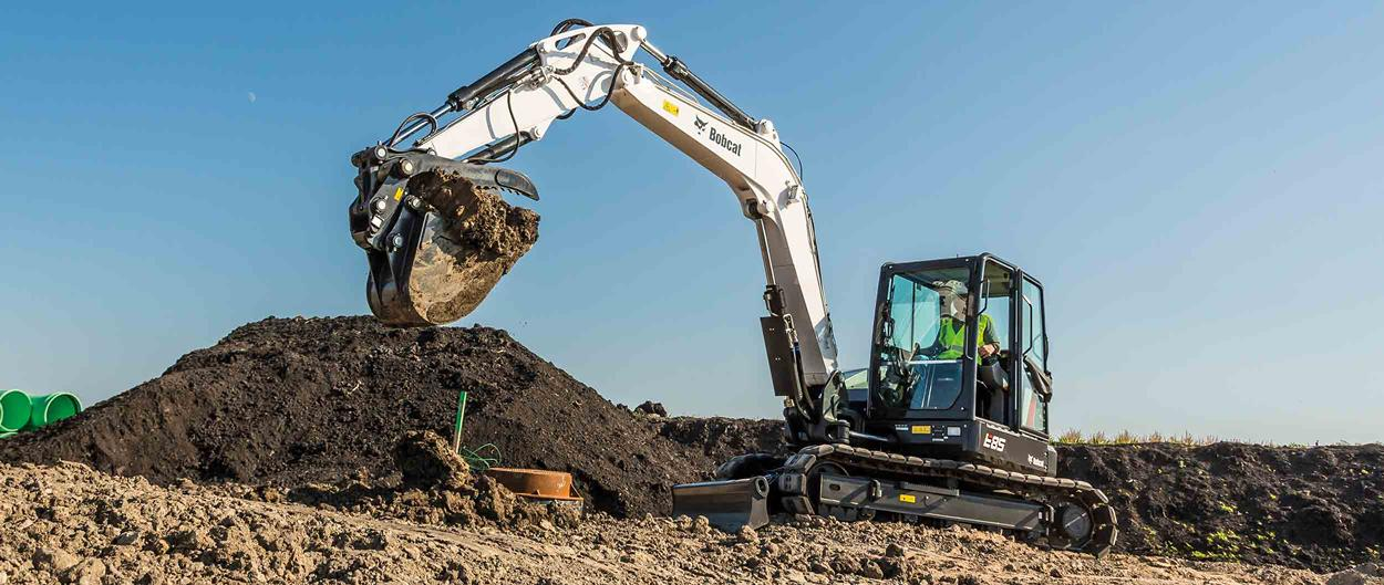 Bobcat E85 compact (mini) excavator and bucket attachment moving dirt.