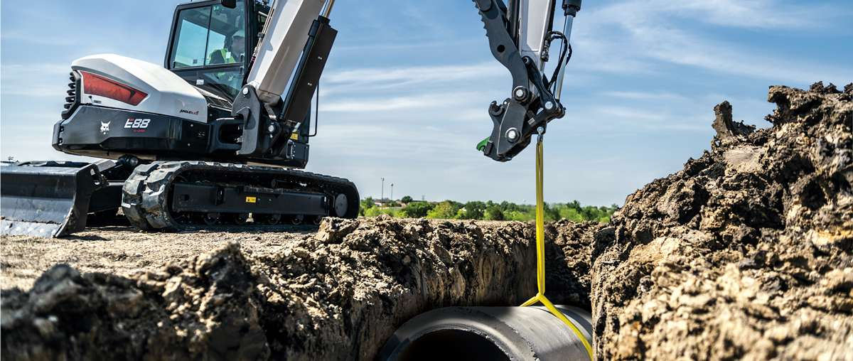 A Bobcat E88 compact excavator places pipe into a trench.