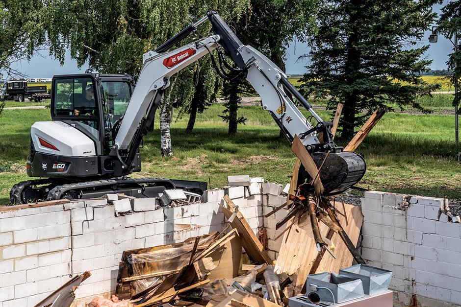 Operator Using Bobcat E60 Mini Excavator With Clamp Attachment To Move Debris On Demolition Site