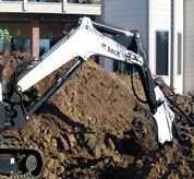 Bobcat compact (mini) excavator with the extendable arm system and bucket attachment.