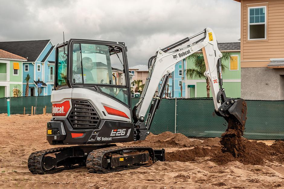 Bobcat E26 R-Series compact (mini) excavator digging dirt near new home construction.