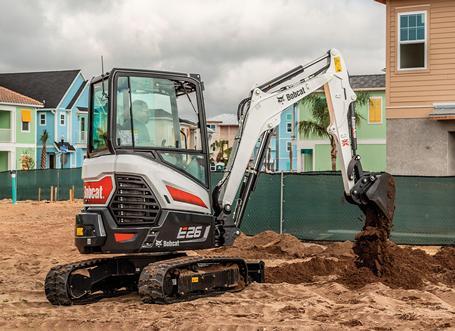 Bobcat E26 R-Series compact (mini) excavator digging dirt near new home construction