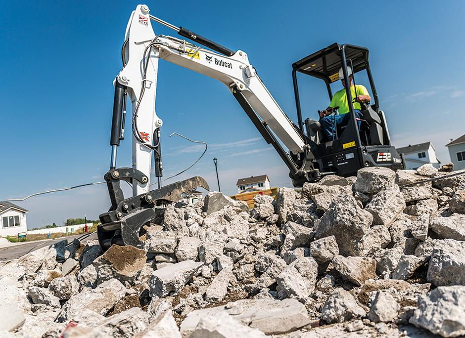 Bobcat E32 R-Series compact excavator digging up concrete.