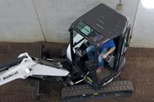 Bobcat compact (mini) excavator with Zero Tail Swing working near a concrete wall.