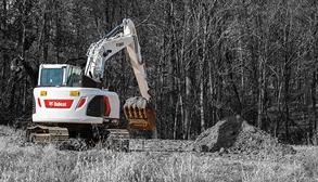 Operator Using Large Excavator To Dig Trench
