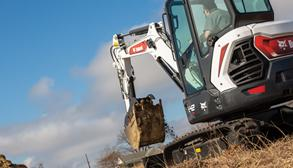 Bobcat Compact Excavator Operator Digging A Hole On A Jobsite.