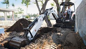 Contractor Digs A Trench Next To A Wall With A Bobcat Mini Excavator