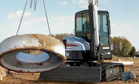 Bobcat E55 compact (mini) excavator lifting a heavy object.