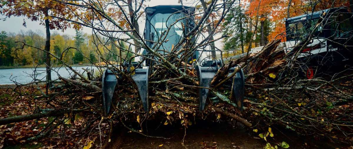 Bobcat Compact Track Loader With Grapple Attachment Moviing Logs.