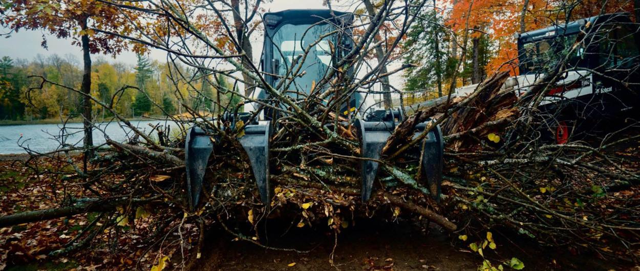 Bobcat Compact Loader With Grapple Attachment Moving Logs And Branches.