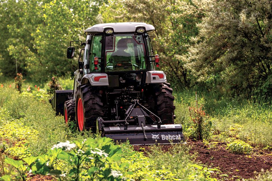 Bobcat compact tractor with 3 point tiller implement.