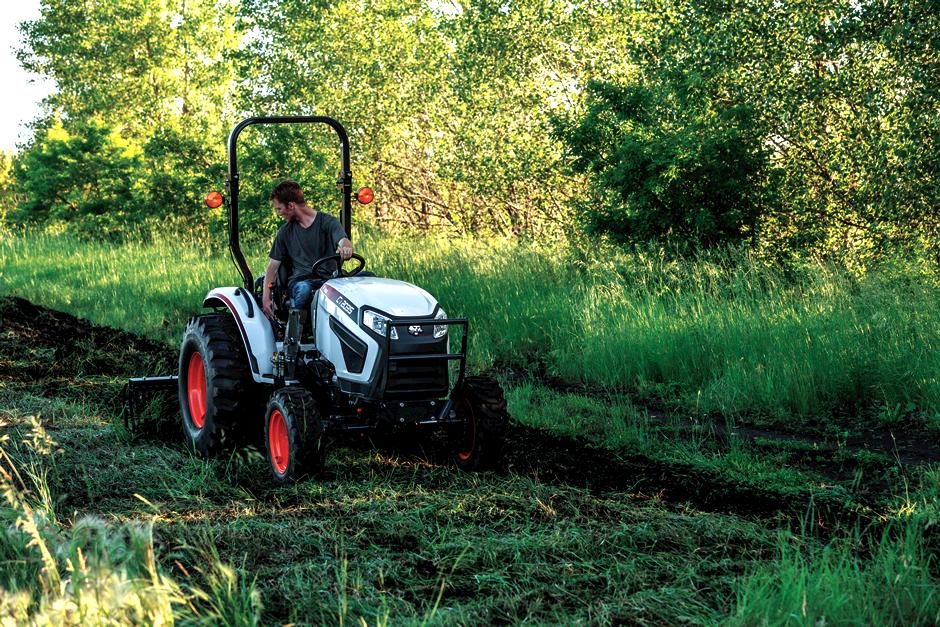 Bobcat sub-compact tractor with 3-point tine rake attachment.