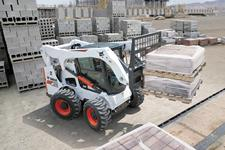 Bobcat A770 all-wheel steer loader lift a pallet of bricks with the pallet fork attachment.