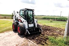 Bobcat A770 all-wheel steer loader working on grass.