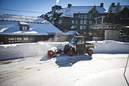 Angle broom attachment on Bobcat 3650 UTV is used to sweep snow on a mountian path.