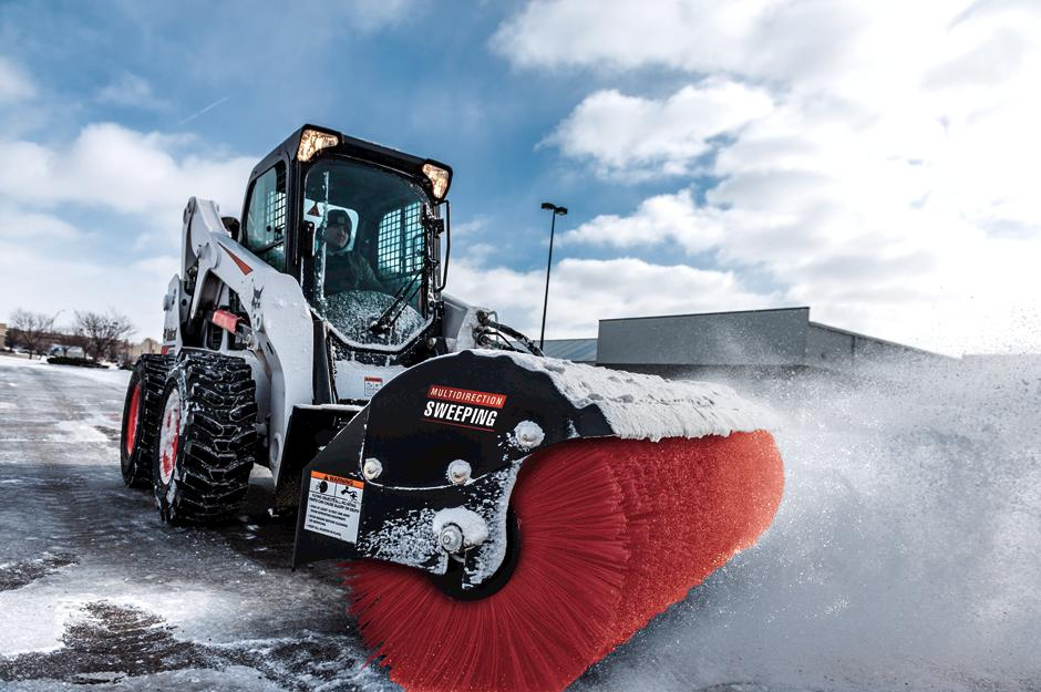 Operator Clears Parking Lot Of Snow With Angle Broom Attachment On Skid-Steer