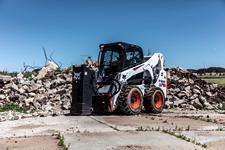 Bobcat S650 skid-steer loader using the Bob-Dock mounting system with a drop hammer attachment.