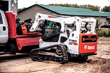 Bobcat T650 compact track loader and Bob-Dock mounting system swapping out attachments on a trailer.