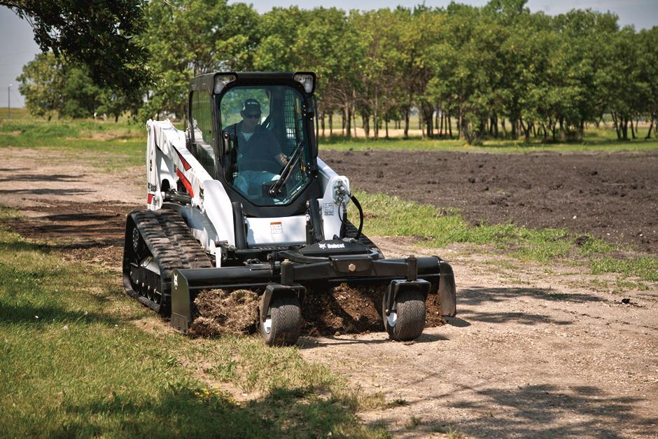 Operator Using Bobcat T630 Compact Track Loader With Box Blade Attachment To Move Soil Down Dirt Road