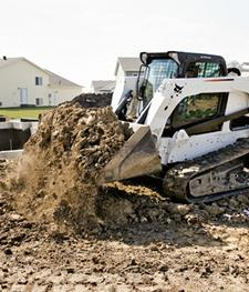A heavy duty bucket attachment is used to lift dirt by a foundation wall.