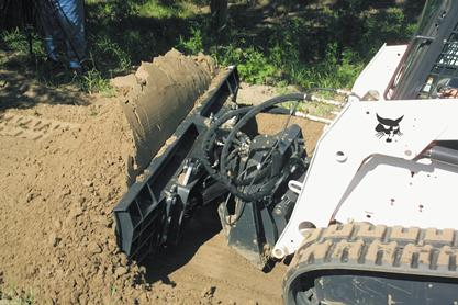 Dozer blade attachment on a Bobcat compact track loader pushes dirt.