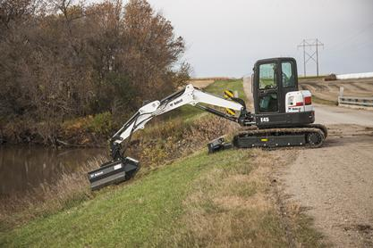 Bobcat E45 compact excavator with flail mower attachment clears weeds in a ditch on the side of a gravel road.