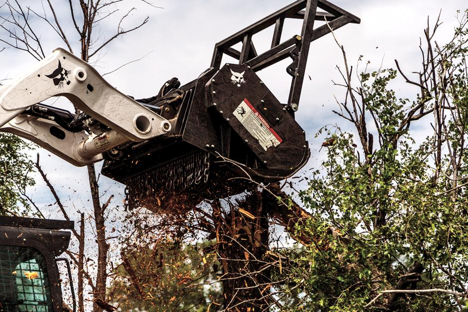 Operator Uses A Bobcat Compact Loader With Brush Cutter Attachment To Take Down A Tree On Land Overgrown With Brush