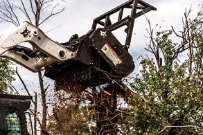 Operator Uses A Bobcat Compact Loader With Forestry Cutter Attachment To Take Down A Tree On Land Overgrown With Brush