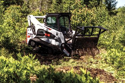 Bobcat forestry cutter attachment plows through brush low to the ground.