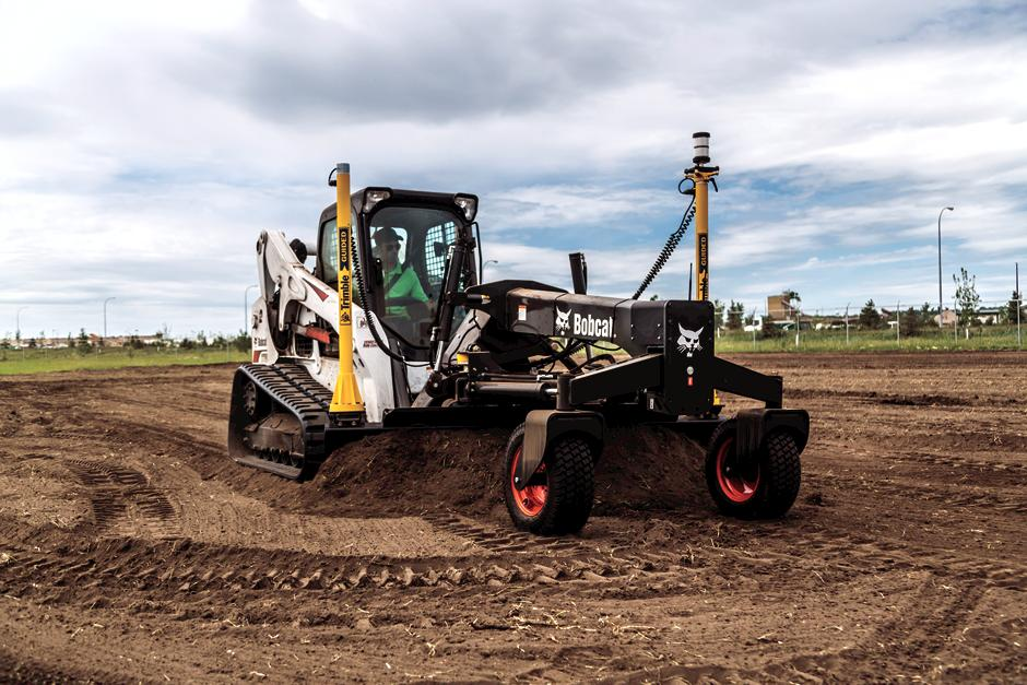 Operator Using Bobcat T770 Compact Track Loader With Grader Attachment To Grade Ground In Dirt Field