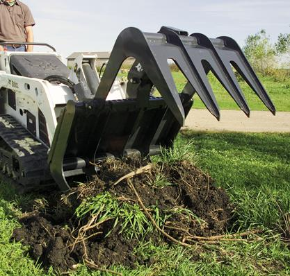 Bobcat root grapple attachment digs into the ground to remove vegetation.