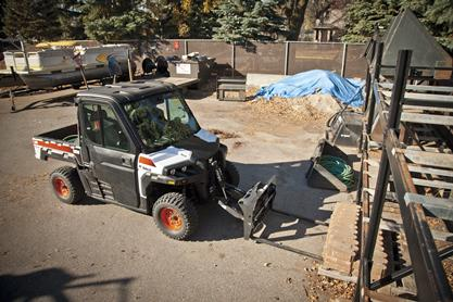 3650 UTV uses Bobcat pallet fork attachment to lift landscaping pavers.