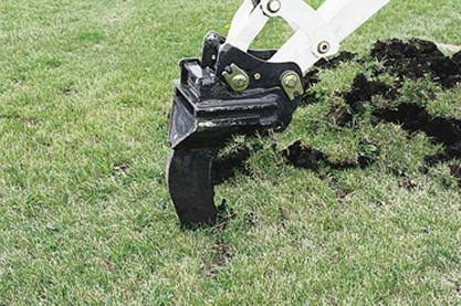 Ripper attachment for Bobcat compact excavators rips through a lawn and soil.