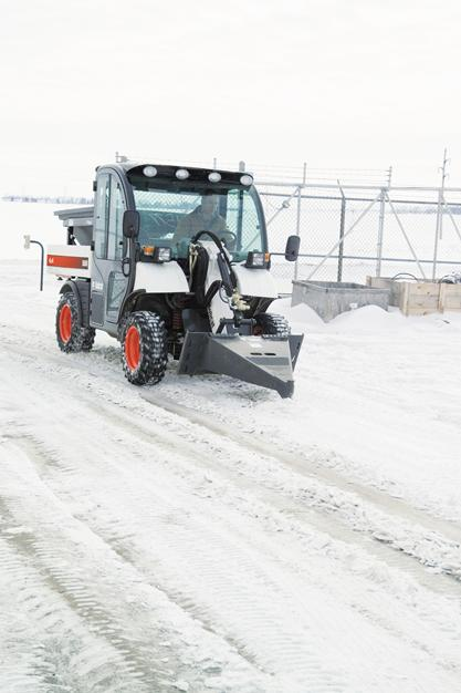 Bobcat scraper attachment is used to remove packed snow from a roadway.