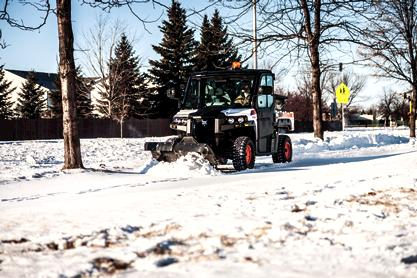 Bobcat 3650 utility vehicle (UTV) and V-blade attachment clearing snow.