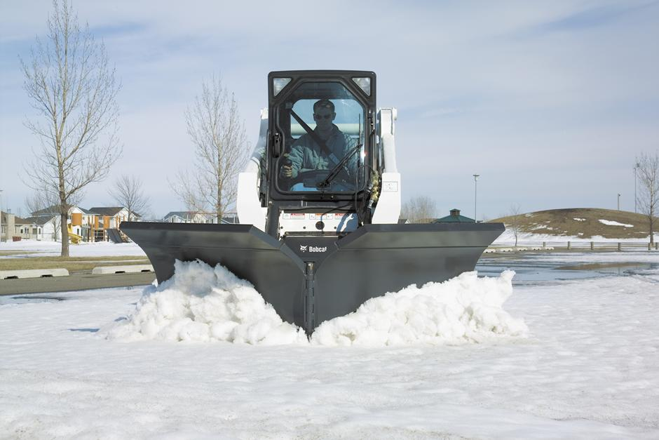 Operator Clears Parking Lot Of Snow With Snow V-Blade Attachment On Skid-Steer Loader