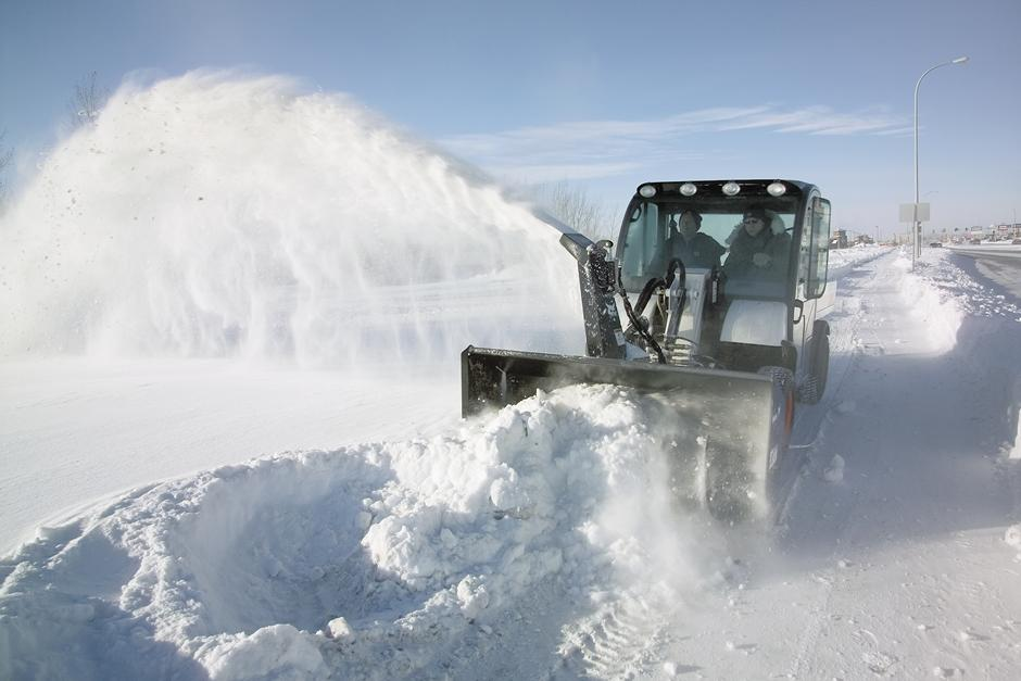 Operator Using 5600 Toolcat Utility Work Machine With Snowblower Attachment To Clear Road