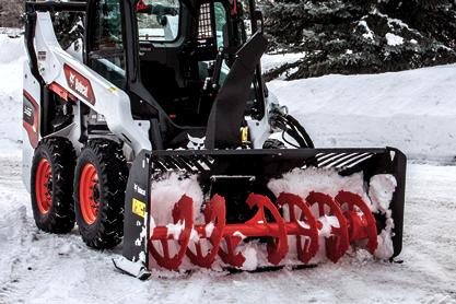 S66 Skid-Steer Loader with snowblower and spreader blowing snow into dump truck in a parking lot.