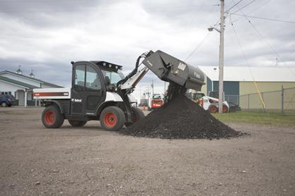 Toolcat utility work machine empties debris from the sweeper attachment into a pile.