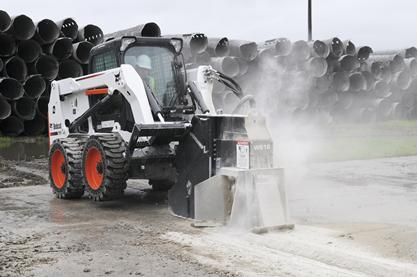 Skid-steer loader with wheel saw cuts through concrete in a parking lot.