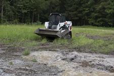 Bobcat T550 Compact Track Loader Navigating Muddy Terrain