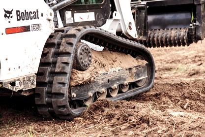 Bobcat T550 compact track loader drives through sandy soil.