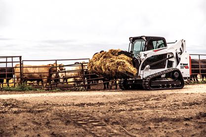 Bobcat T590 compact track loader carrying hay on a cattle farm with a grapple attachment