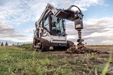Bobcat T590 and auger attachment drill a hole in an open field.