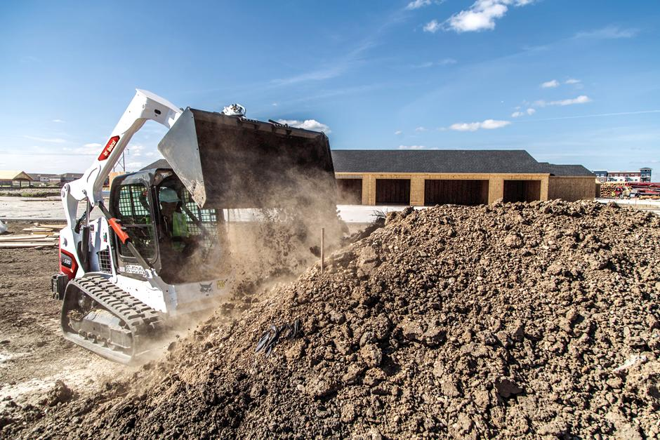 Operator Using Bobcat T595 Compact Track Loader With Bucket Attachment To Dump Dirt Onto Pile On Construction Site