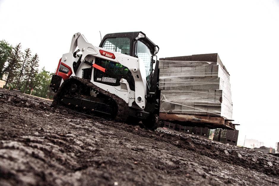 Operator Using Bobcat T595 Compact Track Loader With Pallet Fork Attachment To Move Material On Jobsite