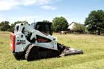 Bobcat T650 compact track loader and mower attachment.
